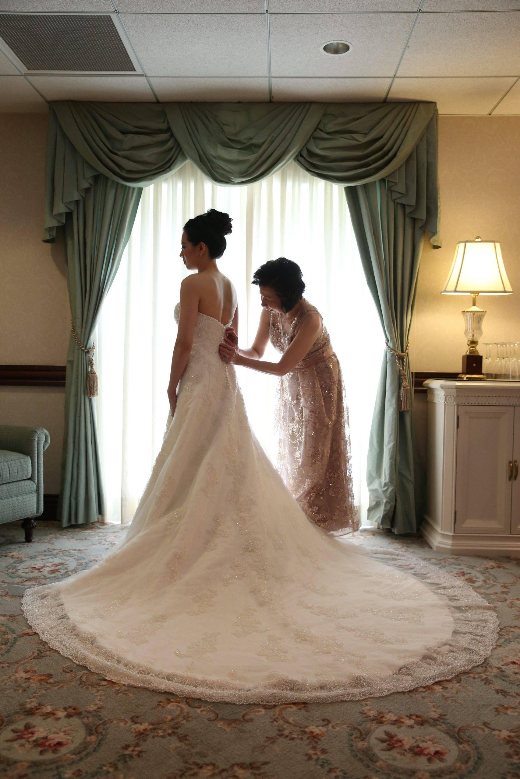 Brooklake mother of the bride helping bride get dressed