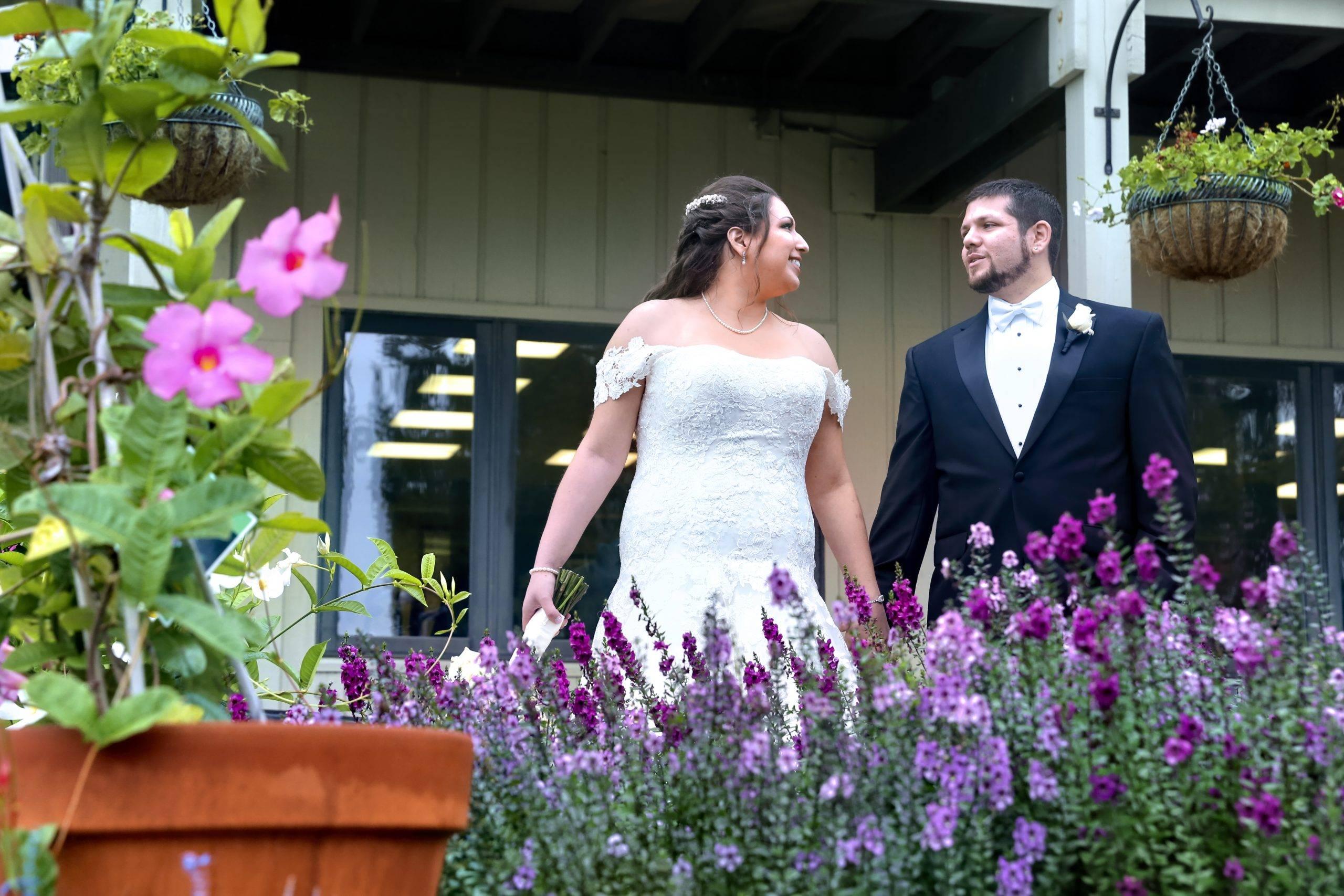 Basking Ridge CC wedding couple by flowers