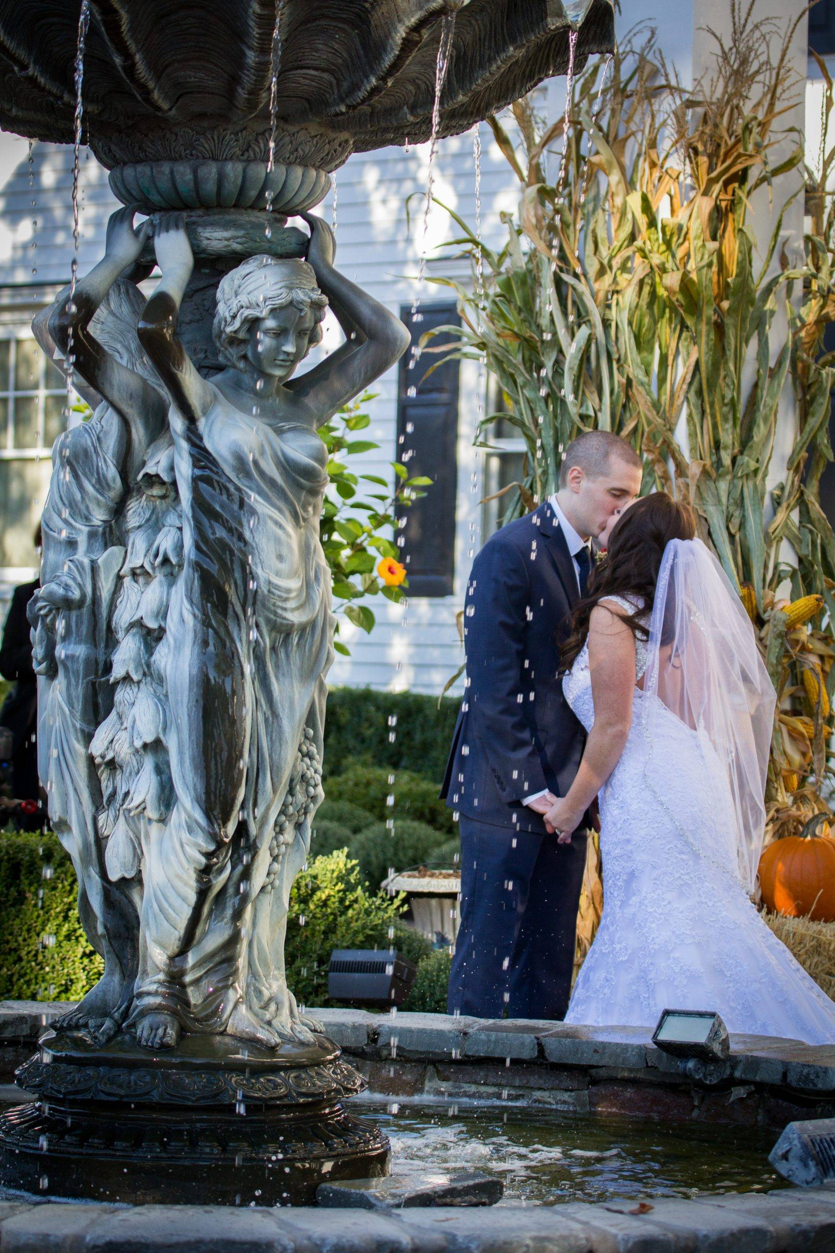 Park Savoy bride and groom kissing by fountain