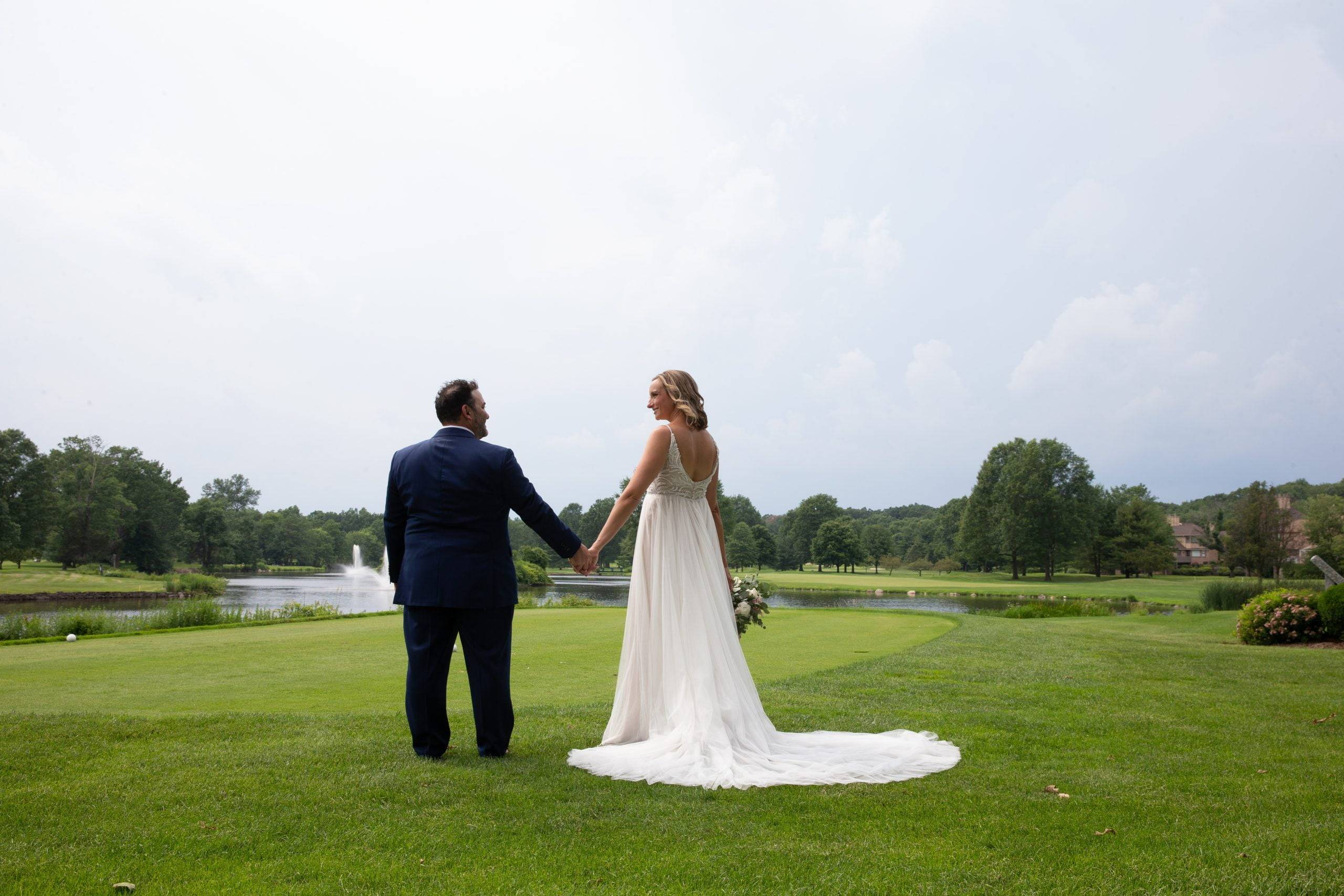 Brooklake bride and groom holding hands by the lake