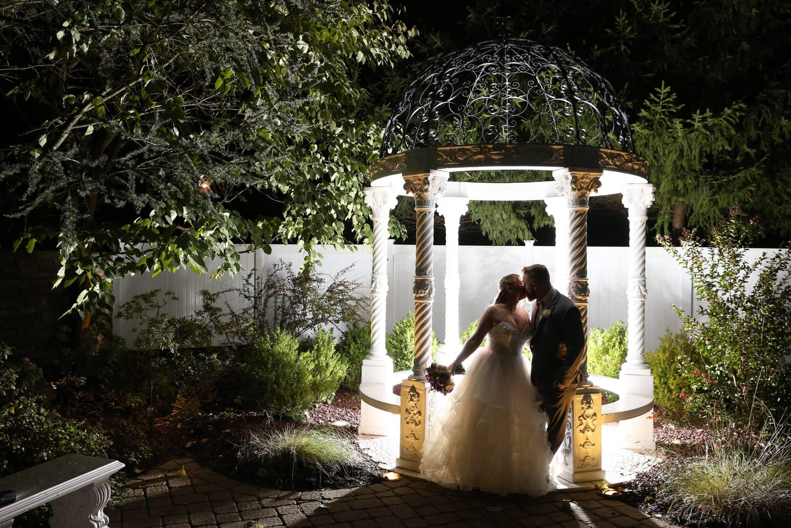 Primavera Regency bride and groom by lighted gazebo at night