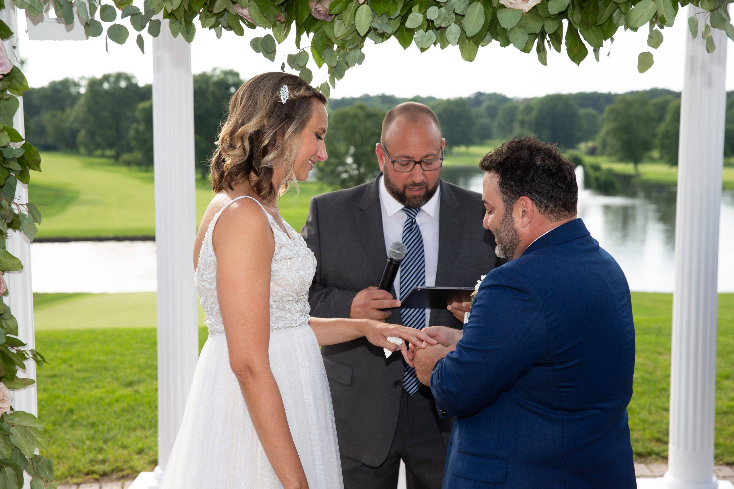 Brooklake bride and groom exchanging rings by the lake