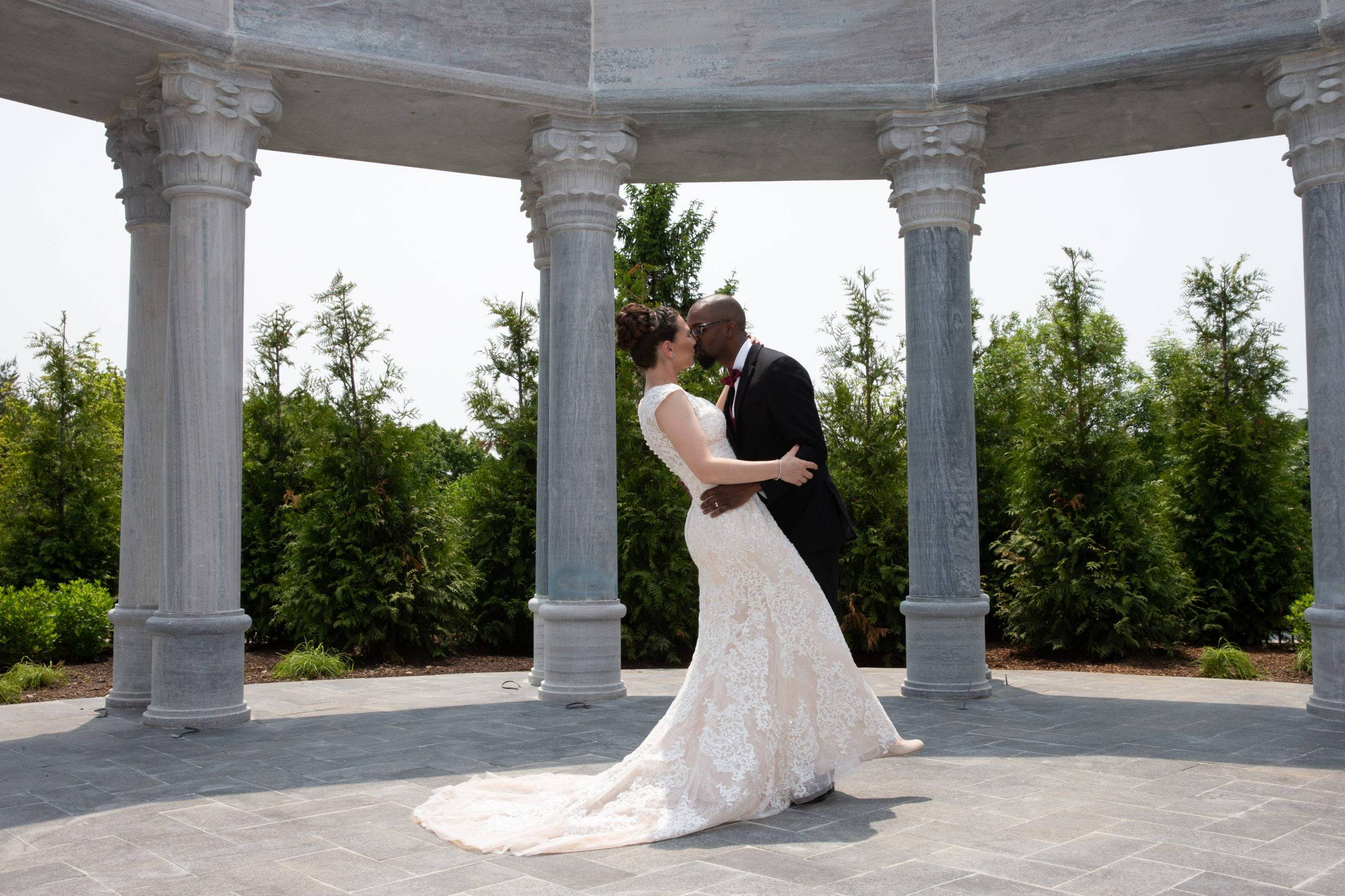 Meadow Wood wedding couple kiss outside by columns